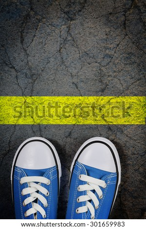 sneakers on cracked concrete surface with a painted yellow line - stock photo
