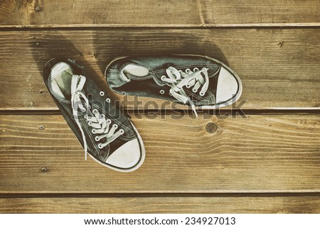 Sneakers on floor on wooden background  - stock photo