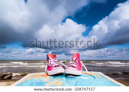 Sneakers on the opened atlas book  - stock photo