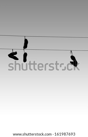 Sneakers, which are tied together and thrown over a electrical line / Hanging sneakers  - stock photo