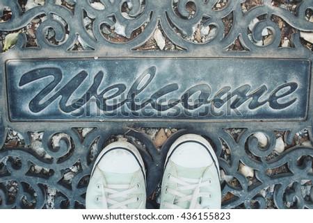Sneakers with doormat - stock photo