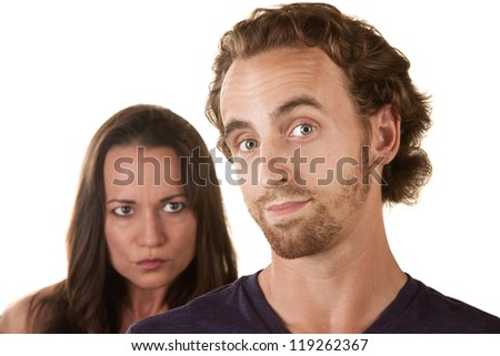 Sneaking male with suspicious woman behind him - stock photo