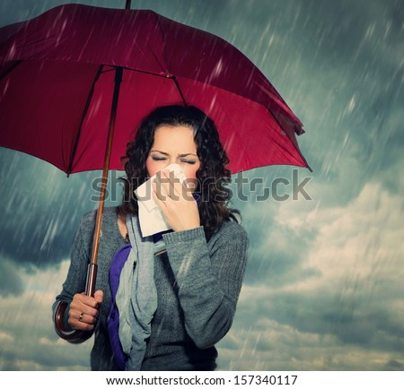 Sneezing Woman with Umbrella over Autumn Rain Background. Sick Woman outdoors. Flu. Girl Caught Cold. Sneezing into Tissue. Headache. Virus. Bad Weather - stock photo