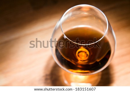 snifter with brandy on old oak table, focus on foreground - stock photo