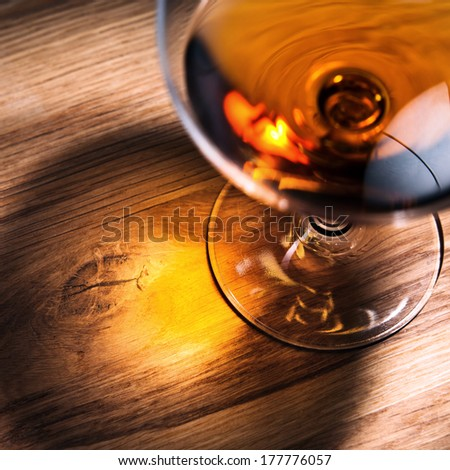 snifter with brandy on old oak table, focus on table - stock photo