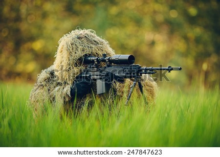 Sniper in the grass looking through the scope - stock photo
