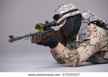 Sniper - military scene shot in a studio over grey background - stock photo