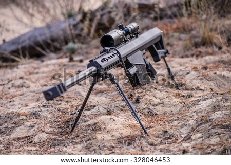 Sniper rifle on bipod with scope on ground background - stock photo