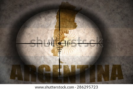 sniper scope aimed at the vintage argentinean flag and map - stock photo