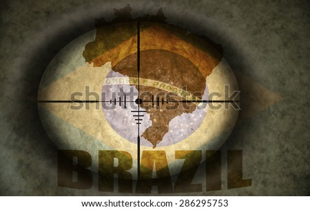 sniper scope aimed at the vintage brazilian flag and map - stock photo