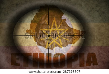 sniper scope aimed at the vintage ethiopian flag and map - stock photo