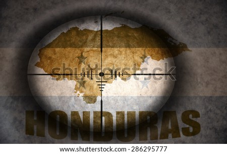 sniper scope aimed at the vintage honduras flag and map - stock photo