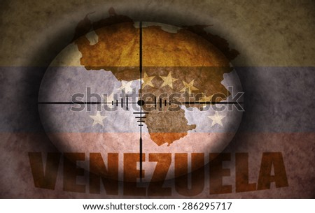 sniper scope aimed at the vintage venezuelan flag and map - stock photo