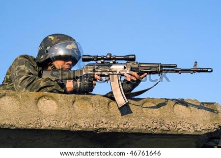 Sniper with machine gun waiting in ambush - stock photo