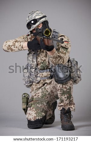 Sniper with rifle aiming over grey background - stock photo
