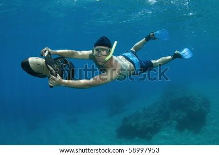 snorkeler rides underwater scooter - stock photo