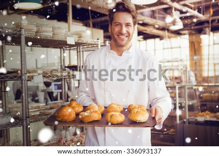 Snow against cheerful baker holding tray of bread - stock photo
