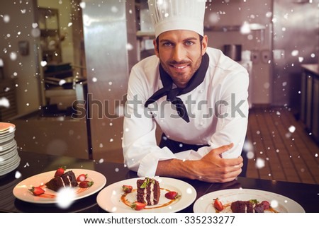 Snow against happy chef looking at camera behind counter of desserts - stock photo