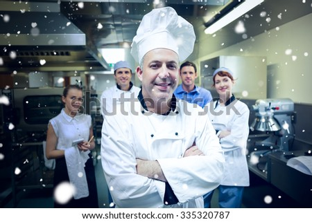Snow against head chef posing with team behind him - stock photo
