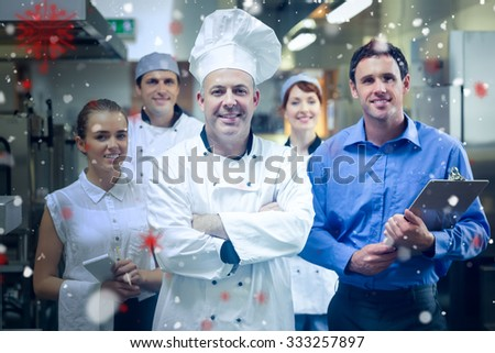 Snow against head chef posing with the team behind him - stock photo