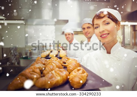 Snow against three young bakers standing in a bakery - stock photo