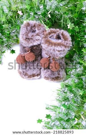 Snow boots with green tinsel - stock photo