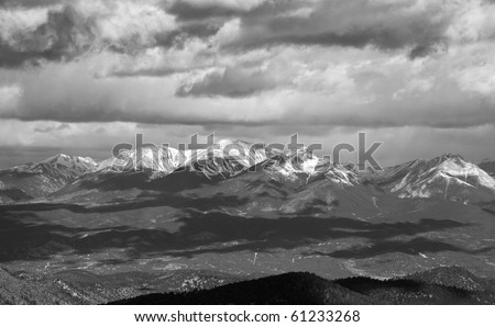 Snow capped mountain range in the Colorado Rockies with cloud shadows and dramatic storm clouds, in black and white - stock photo