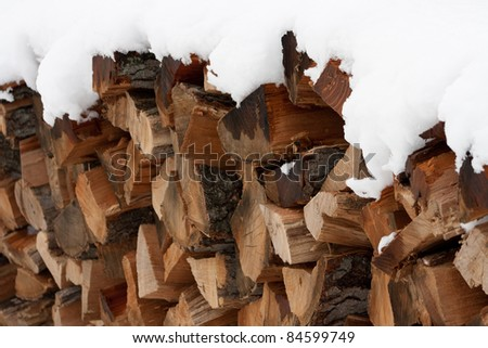 Snow-capped wood pile - stock photo