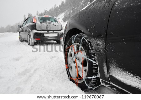 Snow chains on the wheels of the car. Snowy weather - stock photo