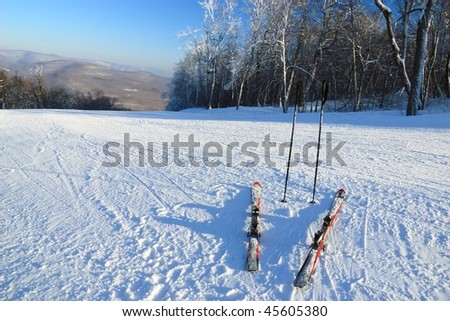 Snow clad skis and poles at the top of a ski trail at Belleayre Mountain Ski Resort in the Catskills Mountains of New York - stock photo