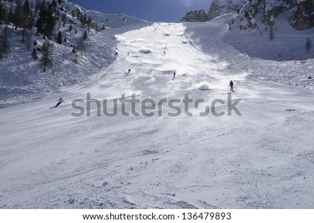 snow clouds on steep ski run #3, Arabba; skiers lift steamy clouds of snow descending steep slope in Dolomites, shot in back-light - stock photo