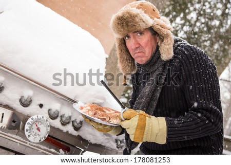 Snow continues to fall on a middle aged man as he goes to light his barbeque only to find it covered in snow in the sub zero temperatures. - stock photo