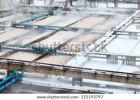 Snow-covered aeration wastewater tanks in sewerage treatment plant - stock photo
