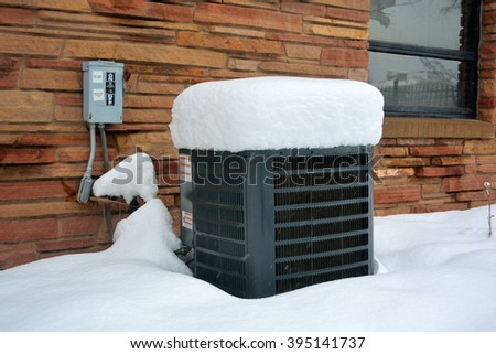 Snow Covered Air Conditioner on a Cold Winter Day - stock photo