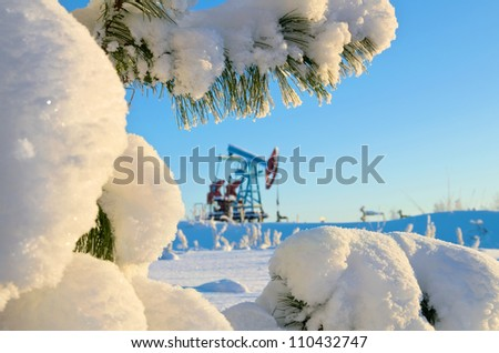Snow-covered branch cedar oil pump in the background - stock photo