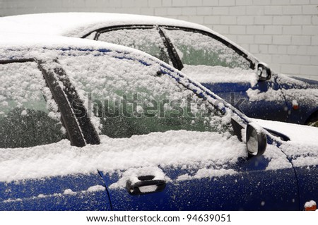 snow-covered cars in town - stock photo