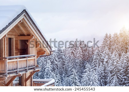 Snow covered chalet in the mountains - stock photo