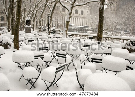 Snow covered coffee tables and chairs in Bryant Park New York City - stock photo