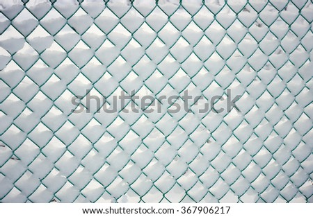 Snow-covered fence, metal mesh in ianuar - stock photo