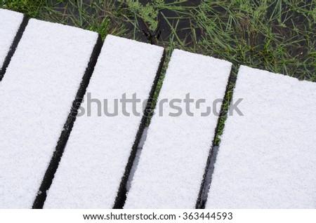 snow covered footbridge, pond - stock photo