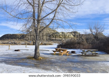 Snow Covered Ground and Picnic Tables in Camp Ground - stock photo