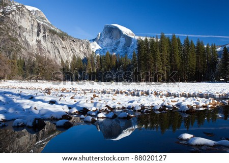 snow covered half dome with reflection at yosemite - stock photo