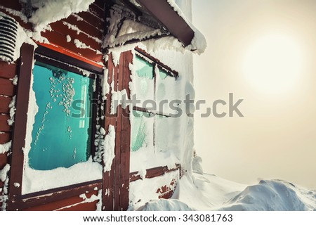 Snow-covered house in the mountains after snowfall. Beautiful winter landscape. - stock photo