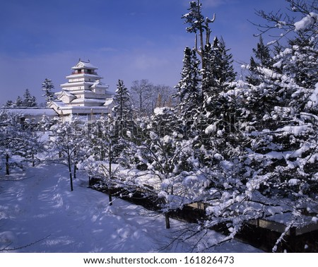 Snow-covered Japanese castle in winter - stock photo