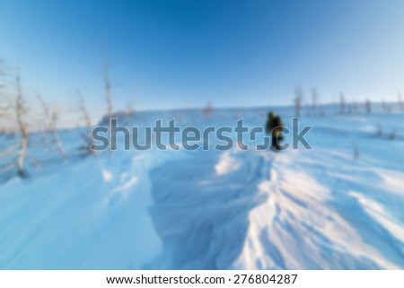 Snow-covered mountain slope with trees. On the slope rises people. Abstract blur background. - stock photo