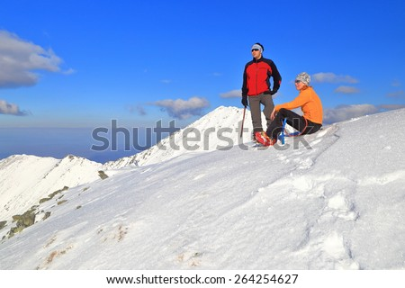Snow covered mountain top and a couple of climbers resting in sunny afternoon - stock photo