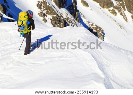 Snow covered mountains and backpacker standing in sunny day - stock photo