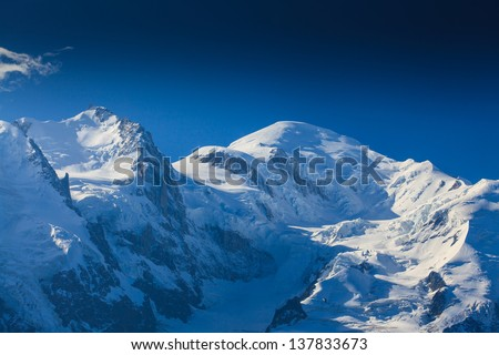Snow covered mountains and rocky peaks in the French Alps, over blue sky - stock photo