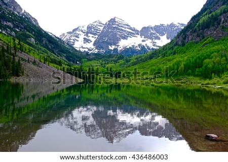 Snow Covered Mountains, Green Trees, Lake and Reflection.  Maroon Bells near Aspen, Colorado State, USA.  - stock photo