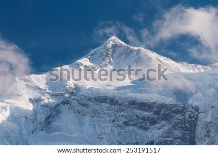 Snow-covered mountains in the area of Annapurna in the clouds under a bright blue sky - stock photo